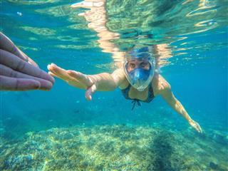 Woman Snorkeling In Blue Sea