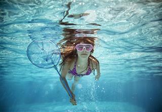 Teenage Girl Swimming With Fish