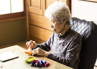 Senior Lady Folding Paper Cranes