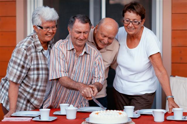 Senior Friends Cutting Cake