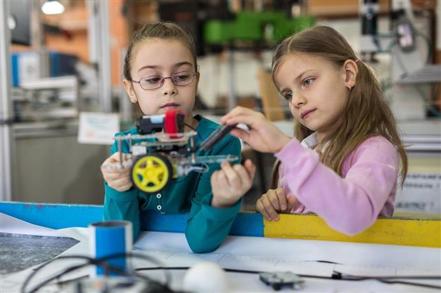 Girls Cooperating While Making Robot