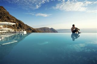 Relaxing Man Sitting Edge Luxury Resort Infinity Pool Santorini Greece