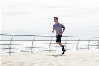 Sports man running outdoors near sea