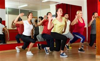 Happy people dancing in gym