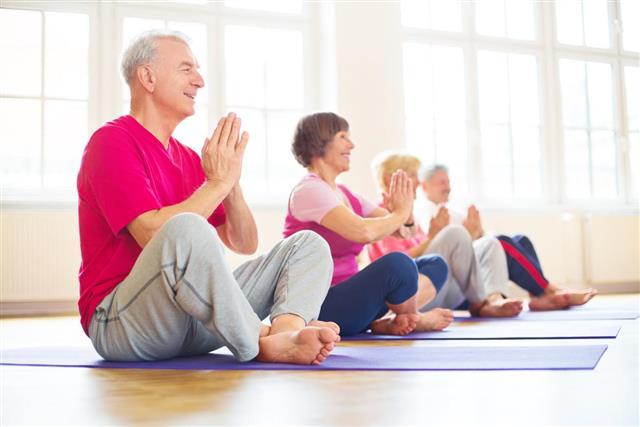 Happy seniors doing yoga