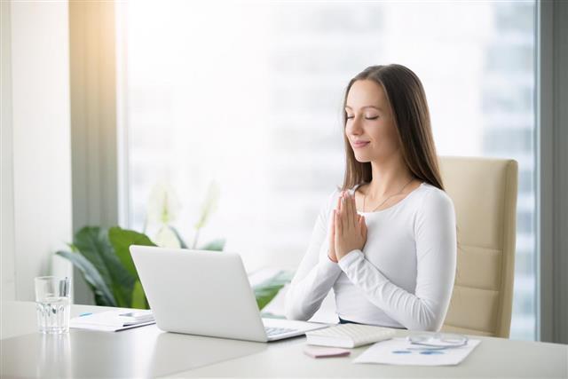 Young woman meditating near laptop