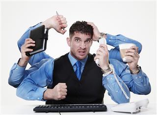 Stressed businessman simulating multitasking with hands