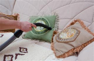 Sofa vacuuming with vacuum cleaner