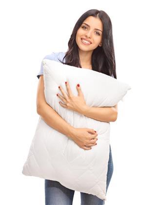Vertical shot of a young woman hugging a pillow