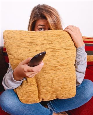 Girl is hiding behind a cushion