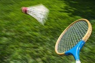 Vintage Badminton Racket Hitting Shuttlecock