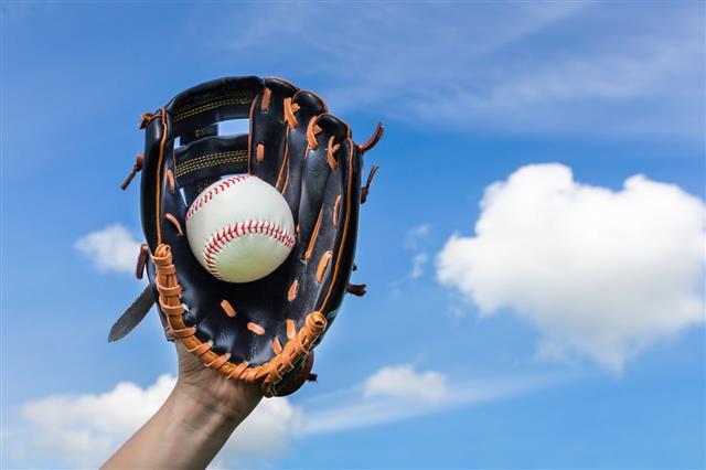 Hand Holding Baseball In Glove