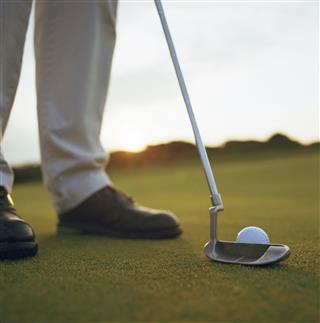 Man Playing Golf At Sunset