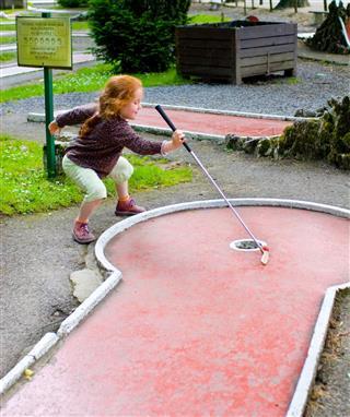 Little Girl Playing Mini Golf