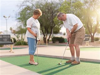 Senior Couple Playing Mini Golf