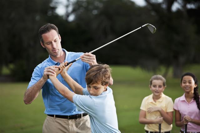 Golf Instructor Adjusting Boys Grip
