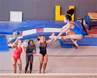 Female Gymnasts Cheer Teammate