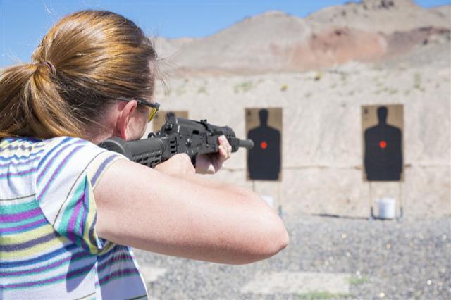 Woman Aiming Rifle At Target