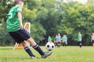 Caucasian Soccer Player Kicks Ball