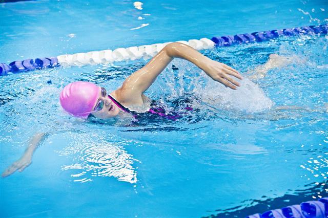 Female Athlete Swimming In Indoor Pool
