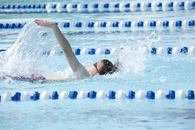 Young Teenage Boy Swimming Backstroke