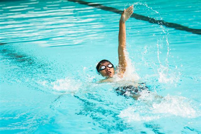 Young Man Swimming Backstroke