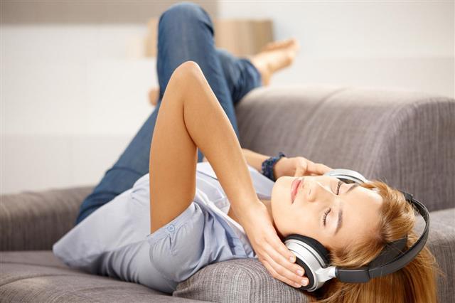 Girl Enjoying Music Laying On Sofa