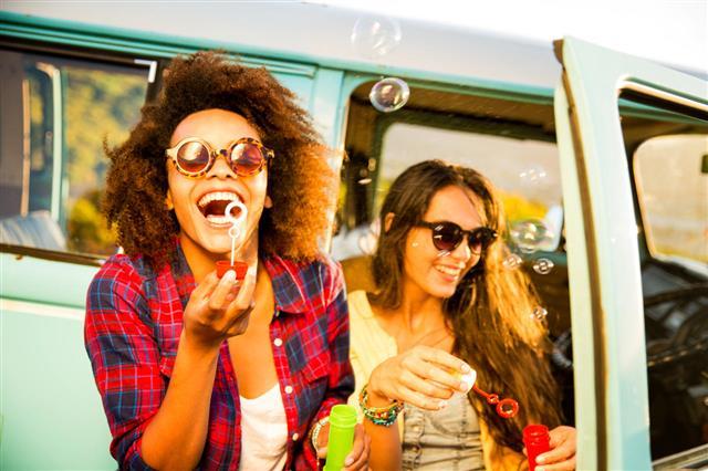 Friends Blowing Bubbles On Road Trip