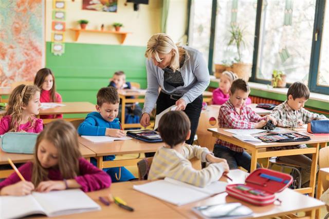 Teacher Assisting Elementary Students