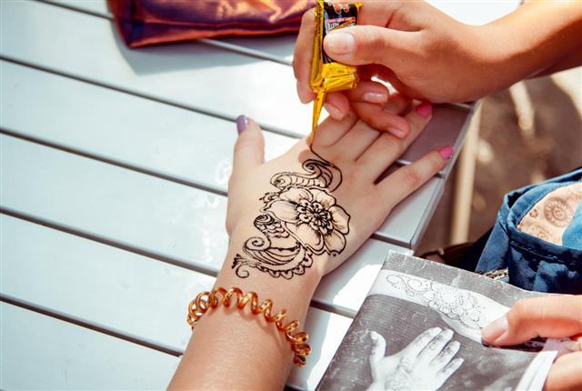 Applying temporary henna tattoo