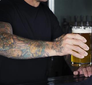 Tattoo hand holding glass