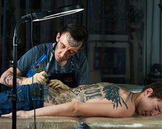 Tattoo artist creating design