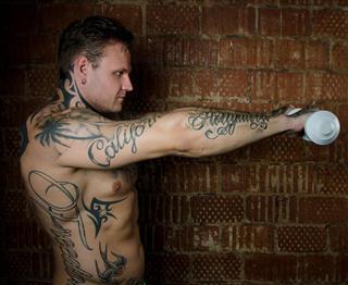 Tattooed man holding dumbbells
