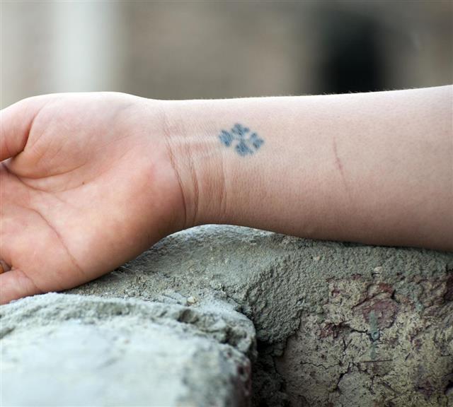 Cross tattoo on wrist