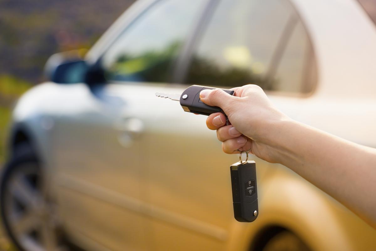 Women's hand presses on the remote control car alarm