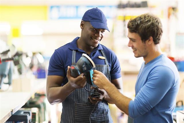 Hardware store worker showing customer a sander