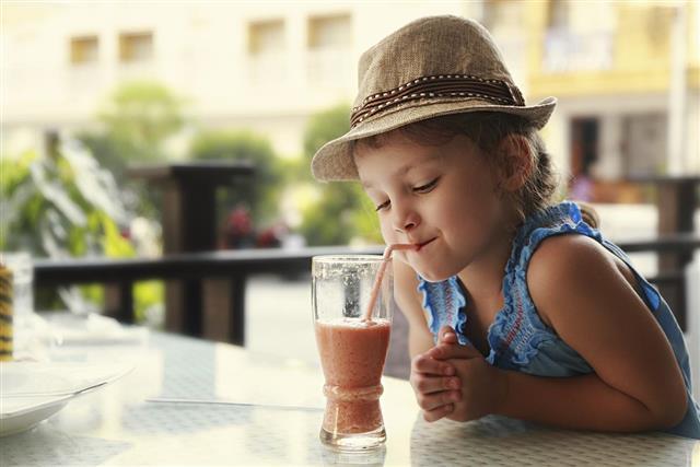 Cute thinking kid girl drinking tasty juice in street restaurant