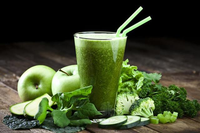 Green vegetable juice on rustic wood table