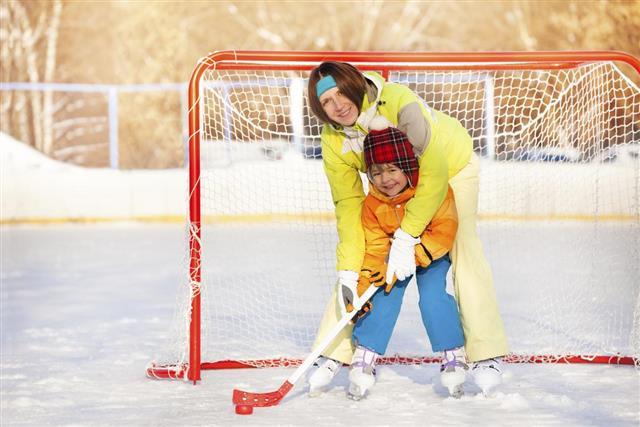 Mom teach boy to play ice hockey