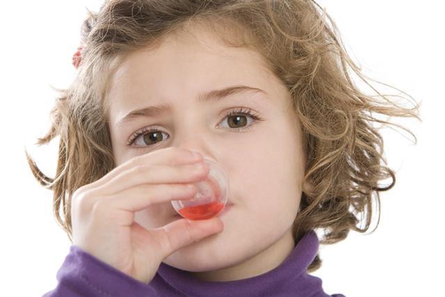 Cute girl drinking her medicine