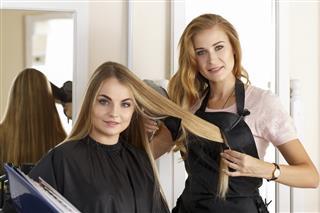 Beautiful blonde female hairdresser holding scissors comb