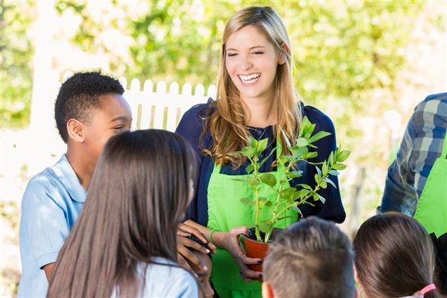 Teacher explaining gardening to elementary student