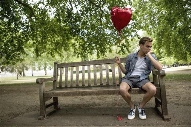 Heartbroken man at the park holding a heart shaped balloon