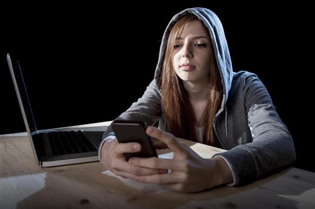 Teenager hacker girl using mobile phone internet cyber crime expert