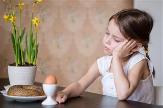 Thoughtful preschooler girl refusing to eat
