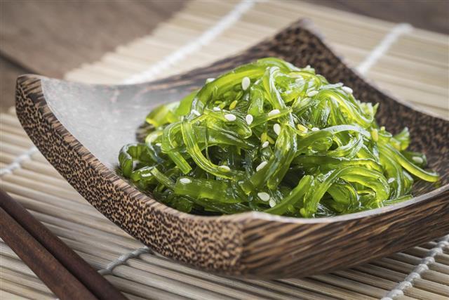 Seaweed salad on wooden plate Japanese cuisine