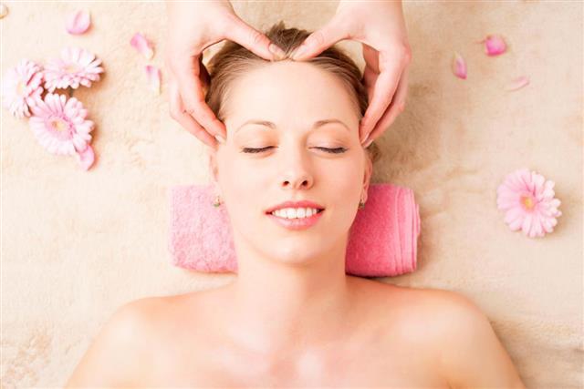 Beautiful woman enjoying facial massage at spa studio