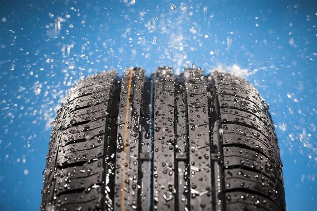 Splashing water on new wet tire against blue background
