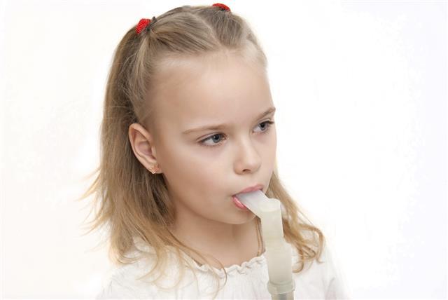 Young girl using inhaler