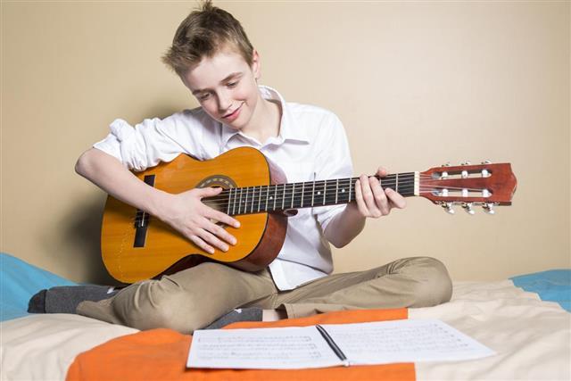 Teenage boy playing guitar in her bedroom